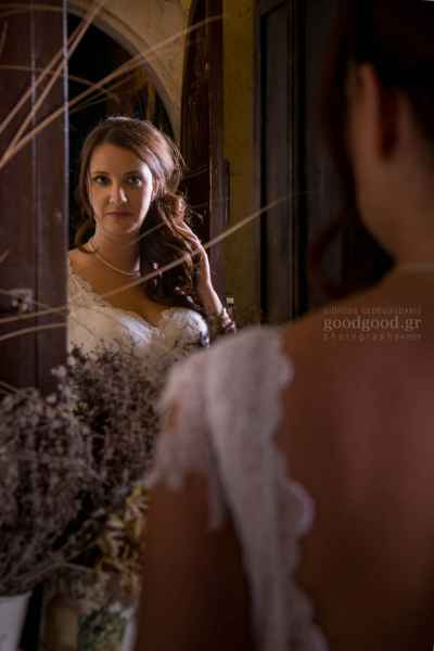Bride in white dress looking at her reflection in the mirror