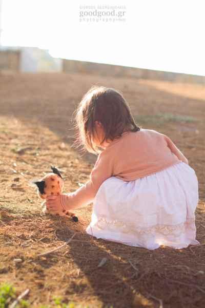 Ένα κοριτσάκι παίζει στο χώμα με την κούκλα του