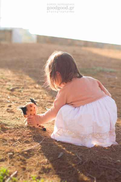 A girl playing in the dirt with her doll