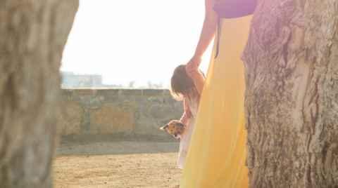 Ένα νήπιο με την μαμά της περπατάνε ανάμεσα σε κορμούς δέντρων στο ηλιοβασίλεμα