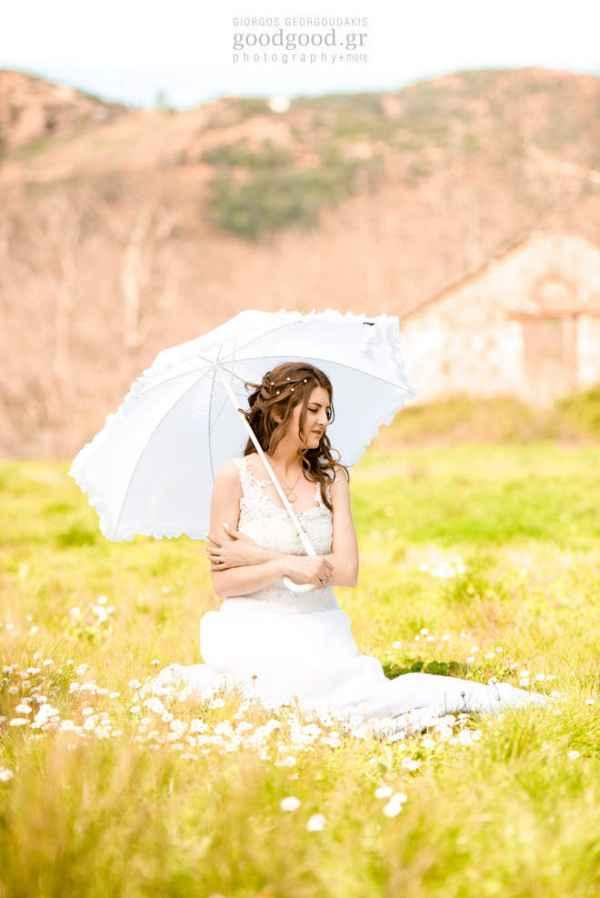 Μία νύφη κάθεται στο χορτάρι και κρατάει μία λευκή ομπρέλα σε φωτογράφιση επόμενης μέρας γάμου
